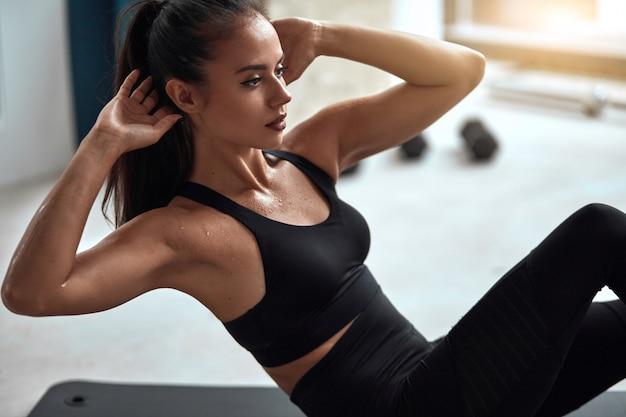Piękna młodej kobiety prasy pompa w gym