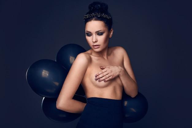Piękna moda naga modelka z czarnymi balonami