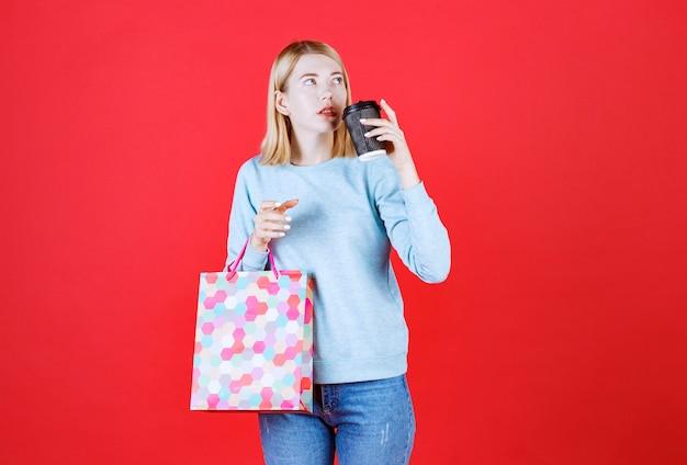 Piękna modelka chce pić swoją kawę, patrząc w górę, trzymając torbę przed czerwoną ścianą