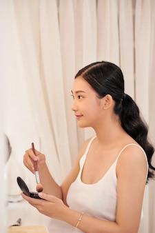 Piękna modelka dziewczyna nakładająca makijaż i uśmiechnięta