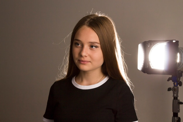 Piękna modelka dziewczyna z długimi blond włosami pozuje w studio w świetle błysków, kontur światła rysuje cienie na jej włosach.