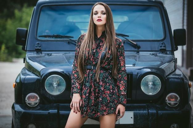 Piękna modelka kobieta z makijażem i fantazyjną sukienką i paskiem obok jeepa na zewnątrz