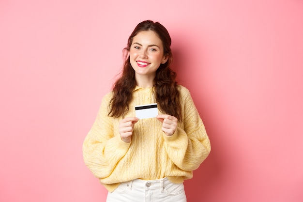 Piękna modelka myśli o zakupach, trzymając plastikową kartę kredytową i uśmiechając się, stojąc przed różową ścianą wiosny. skopiuj miejsce