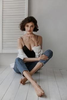 Piękna modelka o szczupłym ciele, ubrana w niebieskie dżinsy i uwodzicielski top, siedzi na podłodze w pomieszczeniu.