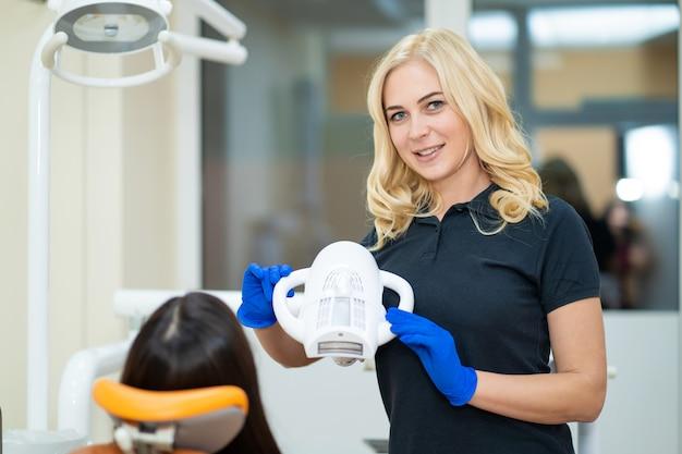Piękna modelka reklamująca wybielanie zębów w klinice dentystycznej z profesjonalnym sprzętem.