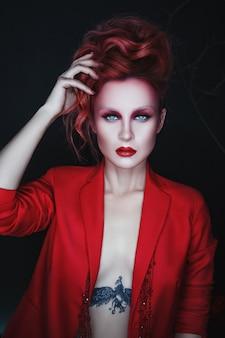 Piękna modelka ubrana na czerwono pozuje w ciemnym surrealistycznym studio