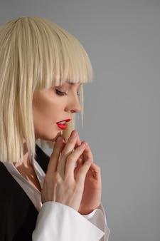 Piękna modelka w białej peruce modląc się przed wybiegiem