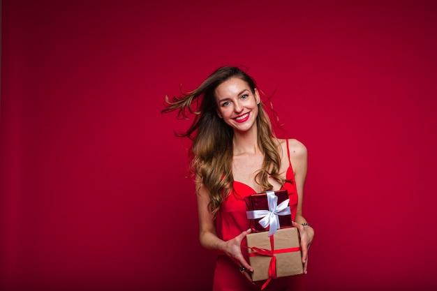 Piękna modelka w czerwonej sukience trzyma wiele małych pudełek z prezentami i raduje się