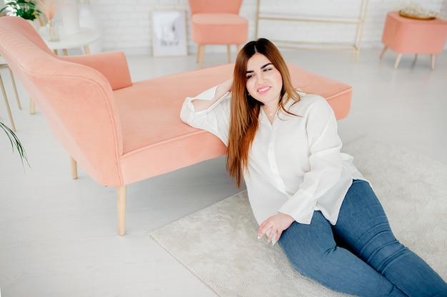 Piękna modelka w dużych rozmiarach ubrana w pustą białą koszulę pozowanie na podłodze