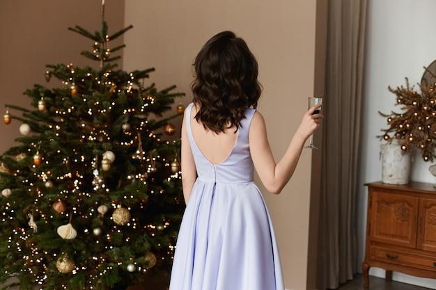 Piękna modelka w eleganckiej różowej sukience z nagimi plecami trzyma kieliszek wina
