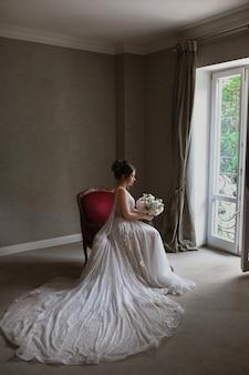 Piękna modelka w luksusowej długiej sukni ślubnej siedzi na krześle we wnętrzu vintage