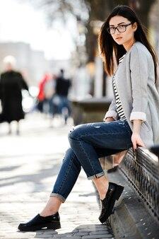 Piękna modelka w okularach siedzi