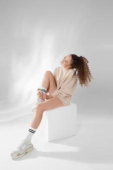 Piękna modelka z afro fryzurą w modnej bluzie i modnych tenisówkach pozuje na białej ścianie