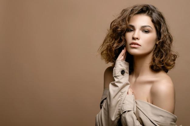 Piękna modelka z czystą skórą i kręconymi włosami w beżowym płaszczu z szalikiem na beżowej ścianie, miejsce
