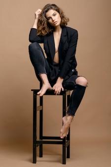 Piękna modelka z czystą skórą i kręconymi włosami w czarnej kurtce na beżowej ścianie na krześle, poważna kobieta biznesu
