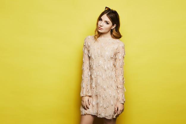 Piękna modelka z delikatnym makijażem, w okularach przeciwsłonecznych i sukience koktajlowej