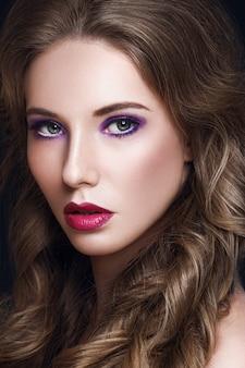 Piękna modelka z długimi kręconymi brązowymi włosami i makijażem