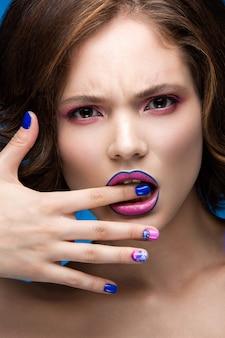 Piękna modelka z jasnym makijażem i kolorowym lakierem do paznokci
