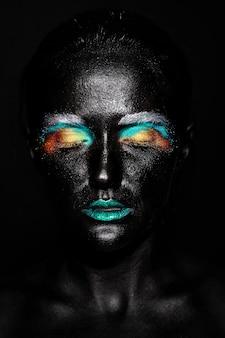 Piękna modelka z kreatywną plastikową niezwykłą czarną maską jasny kolorowy makijaż z czarną twarzą