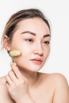 Piękna modelka ze zdrową, świeżą, czystą skórą, ciesząca się masażem jadeitowym wałkiem do twarzy w celu poprawy krążenia, rozluźnienia mięśni i ujędrnienia skóry, na białym tle na szarej ścianie z miejsca na kopię