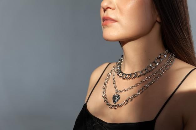 Piękna modelowa brunetka w nowoczesnym srebrnym metalowym naszyjniku z wieloma łańcuszkami