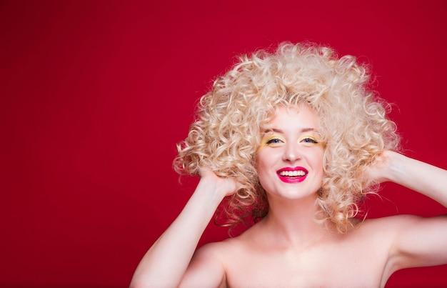 Piękna modna blondynka w stylu retro z obszerną kręconą fryzurą