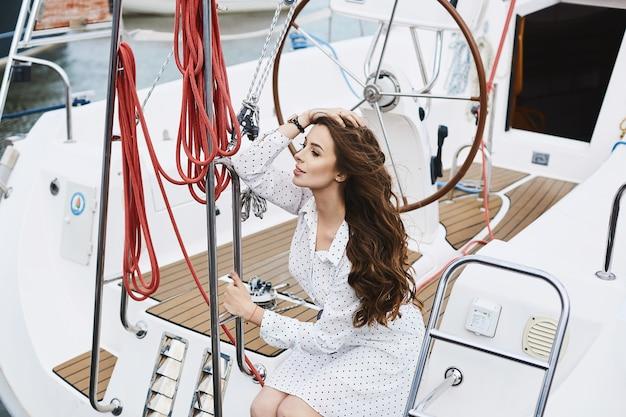 Piękna modna brunetka modelka w białej krótkiej stylowej sukience dostosowująca fryzurę, siedzi i pozuje na jachcie na morzu