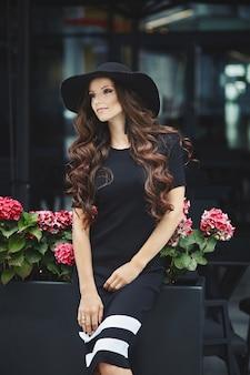 Piękna, modna brunetka modelka w czarnej sukni i kapeluszu pozowanie na zewnątrz, wiosna