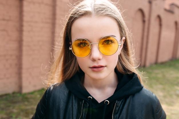 Piękna modna dzieciak dziewczyna w żółtych okularach przeciwsłonecznych w miasto ulicie
