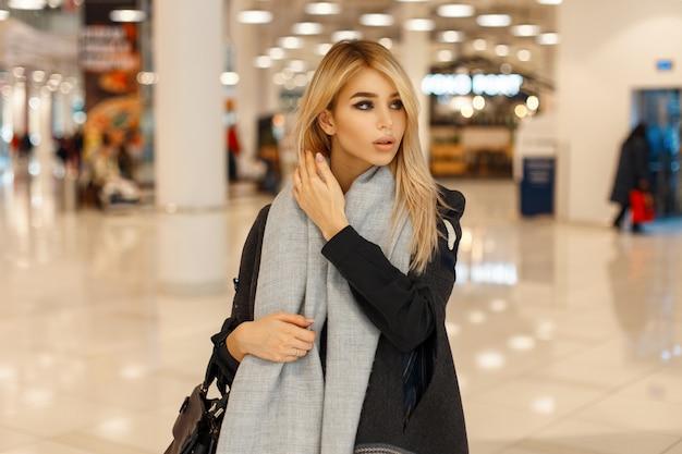 Piękna modna dziewczyna w stylowym płaszczu z szalikiem i torebką w centrum handlowym