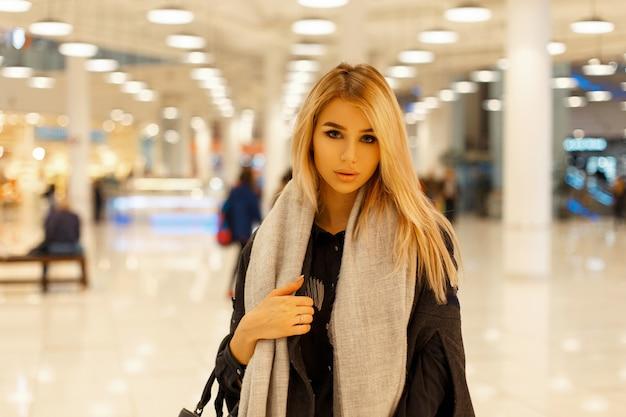 Piękna modna dziewczyna w stylowym płaszczu z szalikiem w centrum handlowym