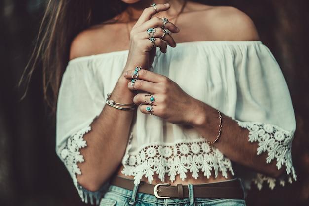 Piękna modna kobieca boho w białej krótkiej bluzce ze srebrną turkusową biżuterią