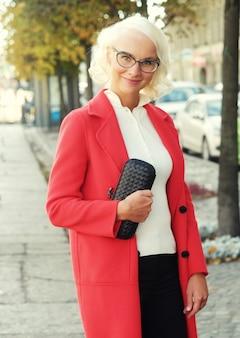 Piękna modna kobieta stojąca na ulicy miasta. jesienny dzień.