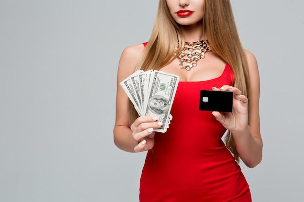 Piękna modna kobieta trzyma pieniądze i kartę kredytową. stylowa szczupła kobieta w czerwonej sukience z czerwonymi ustami, pięknymi włosami, naszyjnikiem.