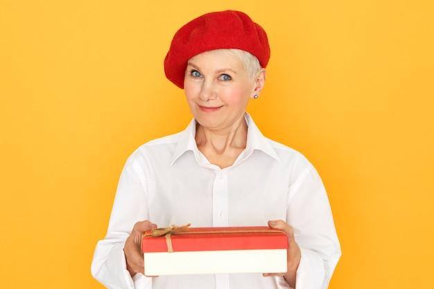 Piękna modna kobieta w średnim wieku w stylowych eleganckich ubraniach obchodzi rocznicę, dając prezent
