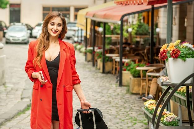 Piękna modna młoda brunetka kobieta spaceru ulicą miasta z walizką podróżną i smartfonem