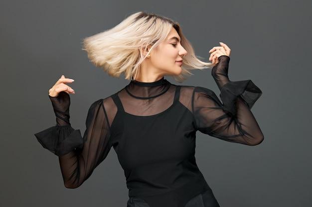 Piękna modna młoda kaukaska kobieta z farbowanymi włosami wyrażająca emocje i uczucia poprzez taniec, poruszająca ciałem przy przyjemnej muzyce, uśmiechnięta. świąteczny nastrój, relaks i koncepcja zabawy