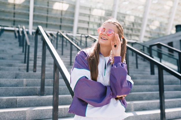 Piękna modna młoda kobieta w stylowe ubrania na sobie różowe okulary i uśmiechnięty
