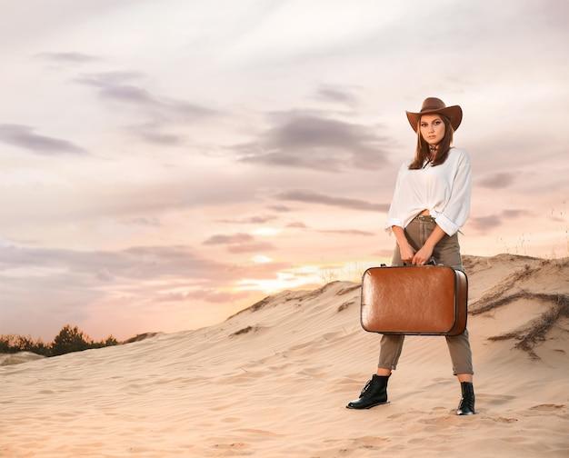Piękna modna młoda kobieta z walizką na pustyni