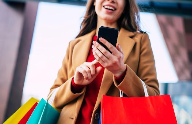 Piękna modna młoda kobieta z wieloma kolorowymi torbami na zakupy w dobrym nastroju ze smartfonem i kartą kredytową podczas spaceru po centrum handlowym w czarny piątek