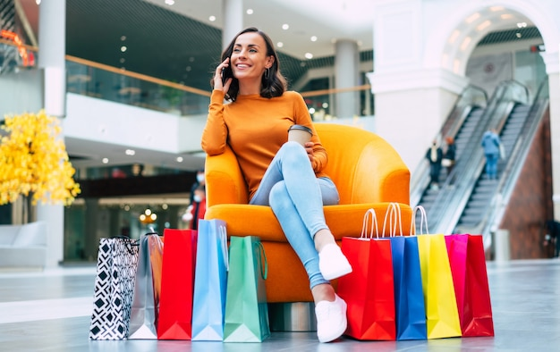 Piękna modna młoda kobieta z wieloma kolorowymi torbami na zakupy w dobrym nastroju ze smartfonem i kartą kredytową, siedząc w centrum handlowym w czarny piątek