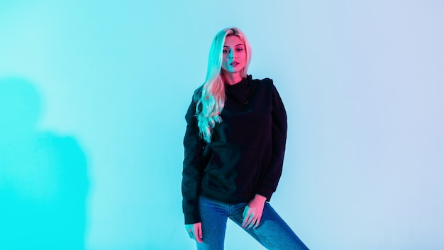Piękna modna modelka z blond włosami w stylowej czarnej bluzie z kapturem i niebieskich dżinsach w studio na jasnym neonowym różowym tle