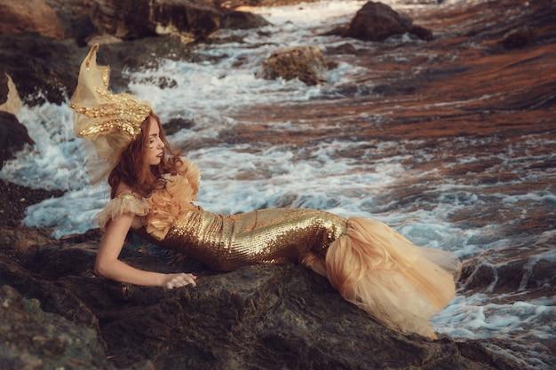 Piękna modna syrenka siedzi na skale nad morzem