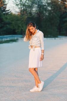 Piękna, modna uśmiechnięta dziewczyna pozuje w stylowej, kobiecej