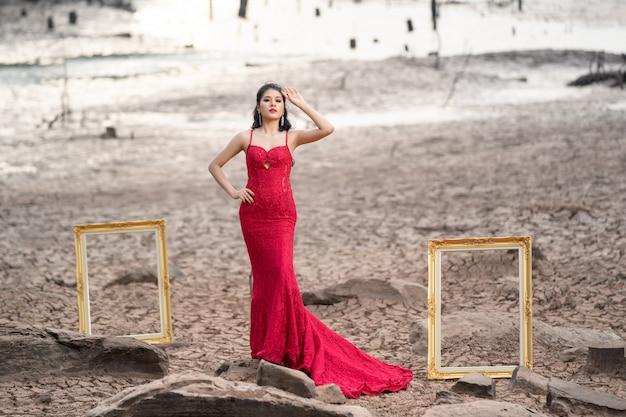 Piękna mody kobieta w jesieni czerwieni sukni z spada liśćmi
