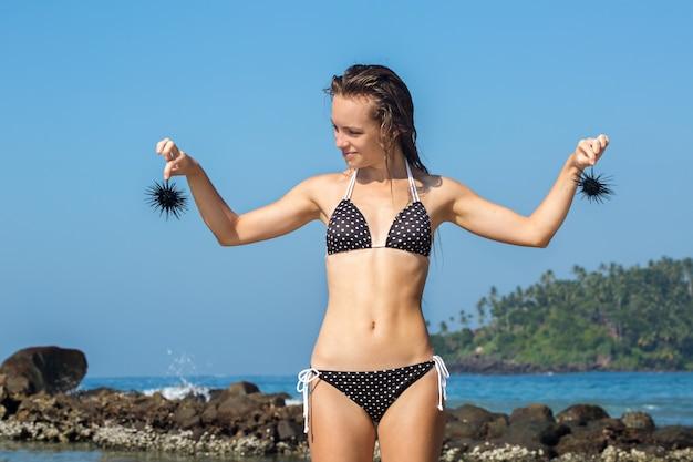 Piękna mokra dziewczyna trzyma jeżowce czarne