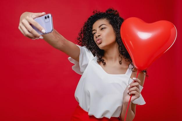 Piękna murzynka robi selfie na telefonie z sercem kształtował balon odizolowywającego nad czerwienią