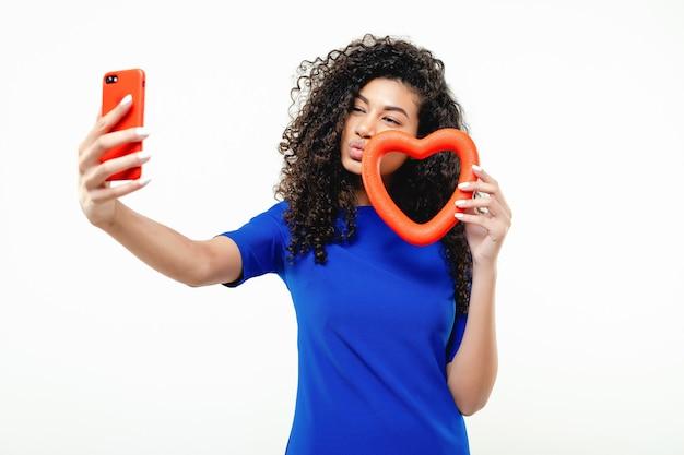 Piękna murzynka robi selfie z czerwonym kierowym kształtem odizolowywającym