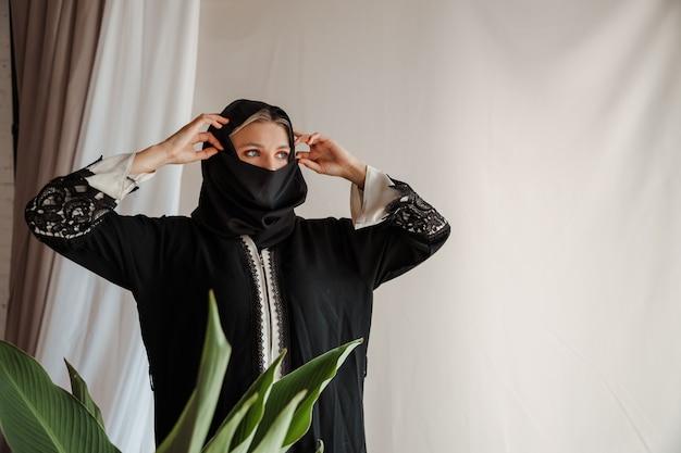 Piękna muzułmanka w tradycyjnej arabskiej sukience abaya na szarym tle