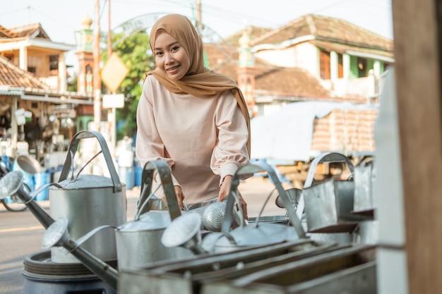 Piękna muzułmanka wybiera konewkę przed sklepem ze sprzętem agd